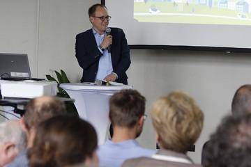 Bild wird vergrößert: Ulrich Hörning fasst mit einem Mikrofon in der Hand die Ergebnisse der Diskussion zusammen