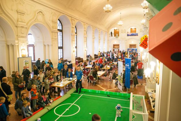 Obere Wandelhalle des Neuen Rathauses mit vielen Menschen. Überall sind Tische mit Spielen aufgebaut. Weiter vorn ist eine Art Fußballfläche mit grünem Teppich und einem Tor sichtbar.