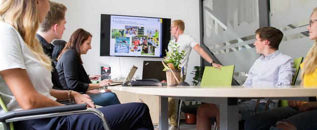 Mehrere Leute sitzen an einem Tisch. Ein Mann steht neben einem Monitor an der Wand, auf dem Lehrinhalte gezeigt werden.