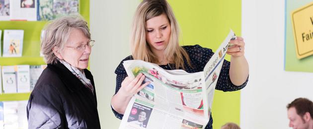 Eine jüngere und eine ältere Frau blicken zusammen in eine Zeitung, im Hintergrund spielt ein Vater mit seinem Sohn
