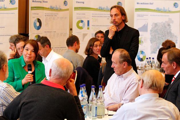 Bürger_innen diskutieren an Tischen, wie Wohnen in Leipzig attraktiv bleiben kann.