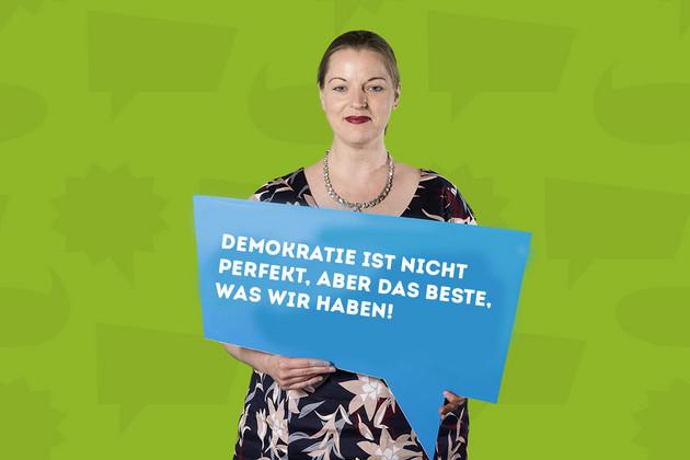 """Die Stadträtin Ute Elisabeth Gabelmann hält ein Schild mit dem Statement """"Demokratie ist nicht perfekt, aber das Beste, was wir haben!""""."""