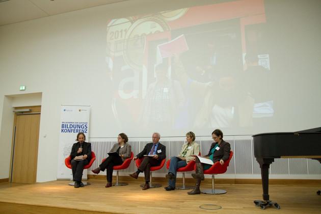 Podium, darauf sitzend drei Damen und zwei Herren. Im Hintergrund eine große Projektion mit Bildern der vierten Bildungskonferenz. Rechts außen ein Flügel.