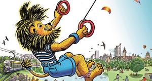 Ein Löwe fliegt an einem Paragliding Schirm über die Stadt Leipzig.