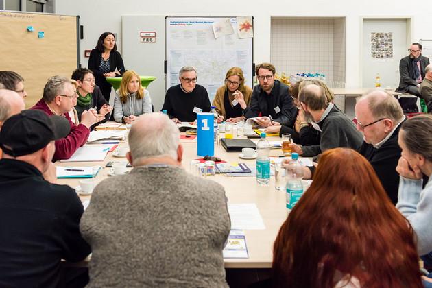 Etwa 15 Menschen sitzen an einem Tisch und diskutieren.