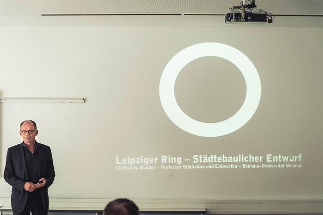 Ein Mann steht links im Bild, rechts neben ihm ist sein Vortrag auf einer weißen Wand sichtbar.
