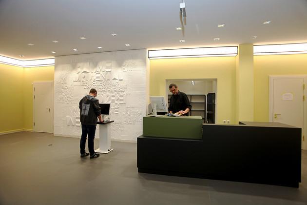 Eingangsfoyer der sanierten Bibliothek Plagwitz mit hellgelben Wänden, grüner Theke, einem Selbstverbuchungsgerät, Wandrelief und Lichtband unter der Decke.