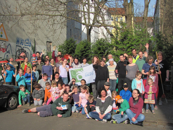 Gruppenbild mit vielen Menschen, die beim Frühjahrsputz mitgemacht haben. Einige winken, andere halten Besen oder Schaufeln in den Händen-