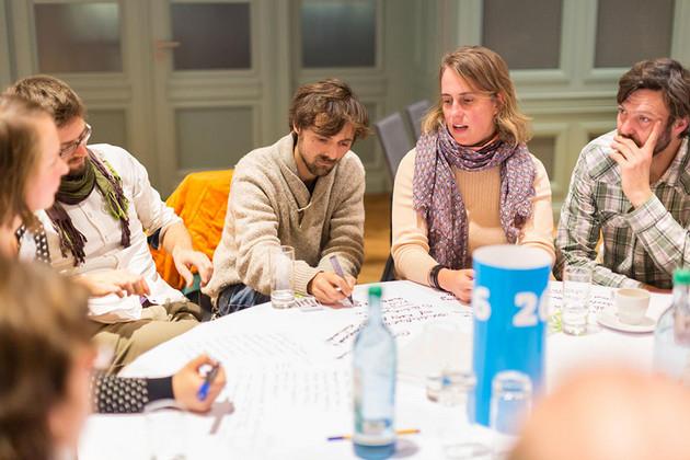 Angeregte Unterhaltung am Tisch: Ein junge Herr schreibt auf die Tischdecke
