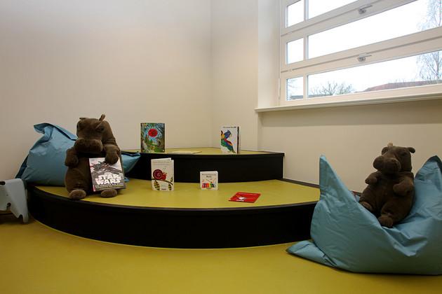 Podest in einer Ecke am Fenster der Kinderbibliothek in Plagwitz mit einer Stufe und grünem Fußboden, darauf zwei Plüschtiere, Kissen und Medien.