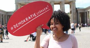 """Junge Frau vor dem Brandenburger Tor zu sehen, die eine rote Sprechblase mit der Aufschrift """"#Demokratie stärken!"""" hält."""