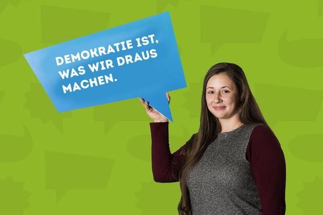 """Die Stadträtin Jessica Heller hält ein Schild mit dem Statement """"Demokratie ist, was wir draus machen.""""."""