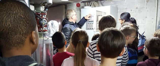 Schüler haben sich vor im Heizungsraum um eine Steuereinheit versammelt und der Hausmeister erklärt die Funktion.
