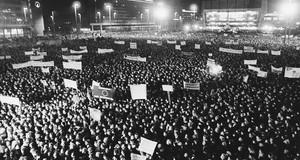 Schwarz-Weiß-Foto einer Demonstration in Leipzig im Herbst 89. Viele Menschen haben sich vor der Oper versammelt. Es sind Transparente zu sehen.