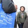 Eine Gruppe von Menschen. In Großaufnahme ein blauer, mit verschiedenen Bildungsbegriffen in weiß bedruckter Stoffbeutel.