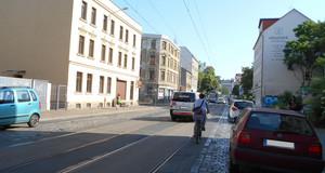 Ansicht der Dieskaustraße mit fahrenden und parkenden Autos und einem Radfahrer. In der Mitte liegen Straßenbahngleise, daneben ist die Straße gepflastert.