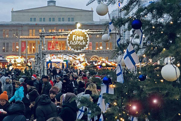 Bild wird vergrößert: Besucher im Finnischen Dorf - Oper Leipzig im Hintergrund