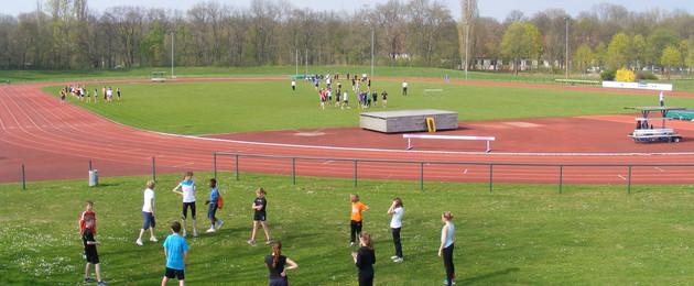 Sportler stehen auf einer Wiese im Kreis und machen Übungen. Im Hintergrund eine Rennbahn i, Leichtathletikstadion Nordanlage Sportforum