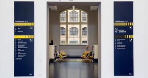 Der Eingang zum LeipzigZimmer ist mit grauer Schrift gekennzeichnet. Man schaut in einen Raum mit Stühlen, Regalen und einem großen Fenster.