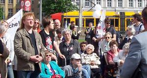 Verschiedene Menschen stehen bei einer Veranstaltung unter freiem Himmel beisammen. Einige sitzen im Rollstuhl.