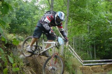 Bild wird vergrößert: Mountainbikefahrer mit Helm fährt einen schlammigen Weg und kleine Hügel herunter