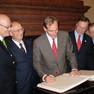 Bürgermeister Burkhard Jung steht neben anderen Männern und trägt sich in das Goldene Buch der Stadt Hannover ein