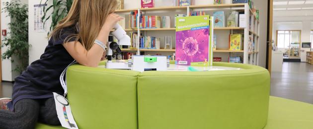 Ein Mädchen schaut in der Kinderbibliothek durch ein Mikroskop