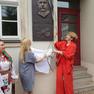 Links im Bild die Leiterin des Kulturamts der Stadt Kiew (eine blonde Dame im blauen Kleid), rechts Frau Dr. Goldfuß von der Stadt Leipzig (in roter Kleidung). Beide haben eben die Gedenkplatte enthüllt und halten noch das Tuch in Händen. Sie schauen hoch zur Gedenktafel an der Hauswand.