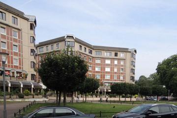 Bild wird vergrößert: Ein Stadtplatz mit Bäumen, Wiese und parkenden Autos. Dahinter Häuser.