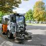 Kleines Fahrzeug mit Bürsten zur Straßen- und Gehwegreinigung auf einem Platz