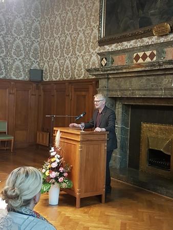 Mann steht hinter einem Rednerpult und spricht zum Publikum