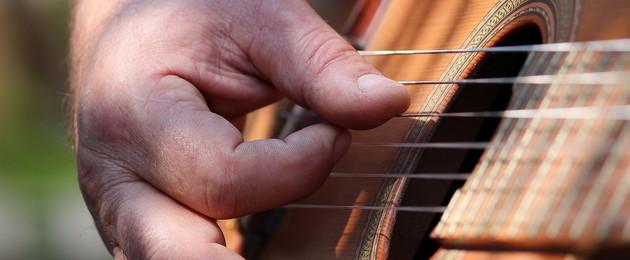 Nahaufnahme einer hand beim Gitarrespielen