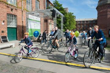 Bild wird vergrößert: Kinder und Erwachsene auf Fahrrädern auf dem Gelände der Baumwollspinnerei