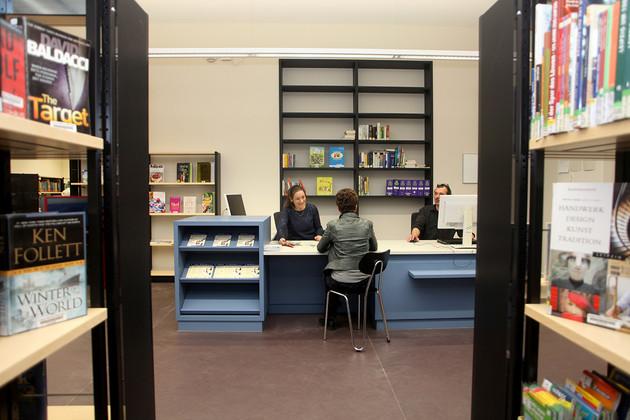 Blick durch die Regale auf einen Beratungsplatz in der Bibliothek Plagwitz mit blauer Theke, dahinter zwei Mitarbeiter, eine Besucherin informiert sich