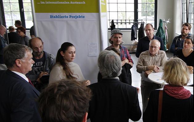 Eine Gruppe von Menschen steht an einem Stehtisch und füllt Projektsteckbriefe aus und redet miteinander.