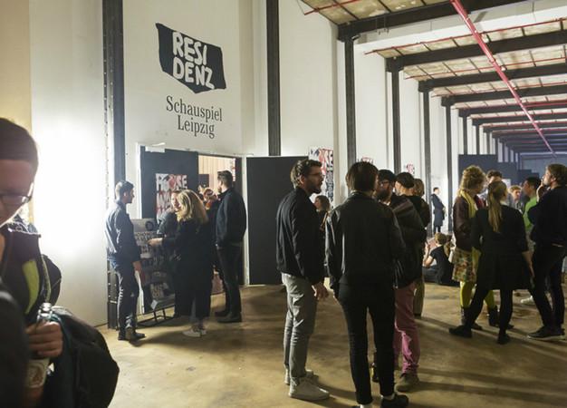 Gruppen von Menschen stehen in einem hohen Halle und unterhalten sich.