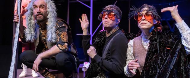 """Drei verkleidete Schauspieler sitzen auf dem Fußboden; Szene aus dem Stück """"Was das Nashorn sah, als es auf die andere Seite des Zauns schaute"""""""