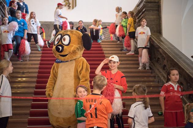 Das Schlingel-Maskottchen steht mit einigen lachenden Kindern vor dem roten Band, welches gleich durchschnitten werden soll.