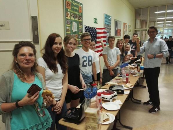 Neun Schüler und Lehrerin Frau Weiske stehen hinter einer langen Tafel mit mehreren Sandwichtoastern und zubereiteten Sandwiches auf Papptellern. Vor der Tafel steht der Lehrer Herr Gans und zeigt mit der rechten Hand das Solidaritätszeichen und hat die linke Hand am Herzen.
