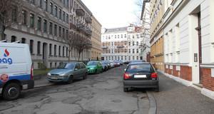 Stark gepflickte Straße mit parkenden Autos