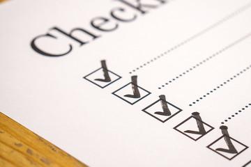"""Bild wird vergrößert: Nahaufnahme einer Checkliste. Man sieht leicht abgeschnitten den Schriftzug """"Checkliste"""" und mehrere Linien untereinander, davor jeweils ein Kästchen mit Haken."""