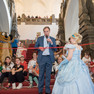 Der Oberbürgermeister zerschneidet ein rotes Band vor der Treppe zur Oberen Wandelhalle. Im Vordergrund assistiert eine Prinzessin im hellblauen Kleid. Im Hintergrund sitzen Kinder auf der Treppe. Links hintenist das Maskotchen Schlingel der LVZ zu sehen.