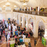 Bild aus der Vogelperspektive von der Oberen Wandelhalle, die mit Messeständen und Menschen gefüllt ist und auf die Empore, die blakonartig im Hintergrund erscheint und ebenfalls voller Messebesucher ist.