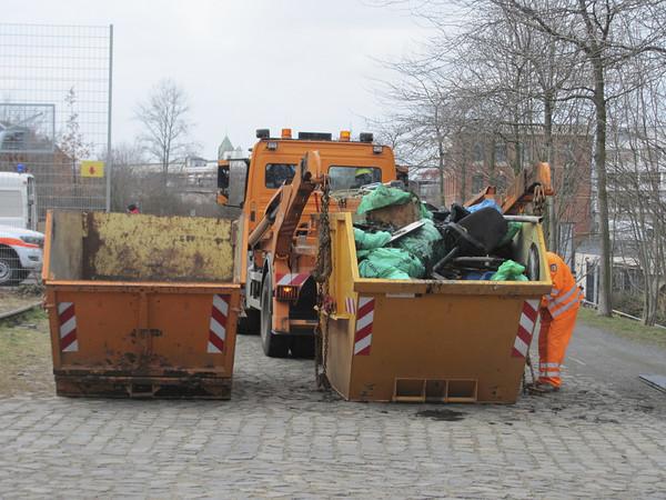 Zwei orange Container. Einer ist voll mit Schrott und wird gerade von einem LKW aufgeladen.