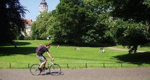 Fahrradfahrer auf einem Weg in einem Leipziger Park. Hinter einer Wiese und Bäumen ist der Turm des Neuen Rathauses sichtbar.