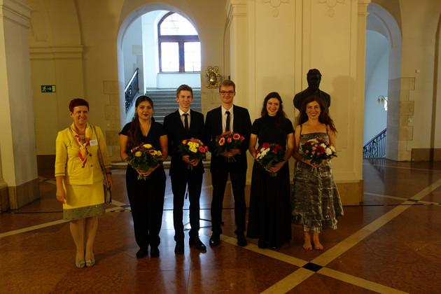 Mehrere Personen mit Blumen in der Hand in der Wandelhalle des Neuen Rathauses
