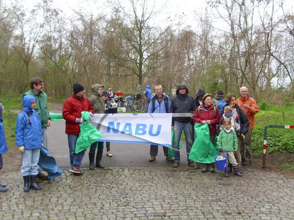 Mitglieder des Naturschutzbundes NABU halten ihr Logo und Mülltüten am Fuße des Fockebergs