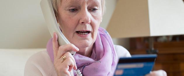 Ältere Frau hält Telefonhörer und Kreditkarte in der Hand