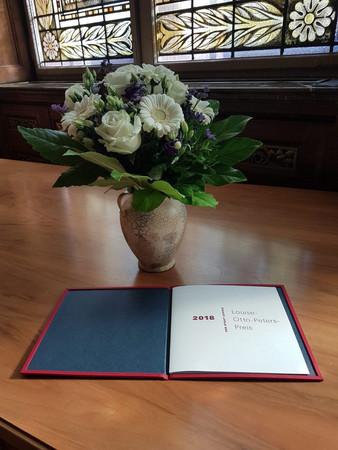 """Eine Urkunde mit dem Schriftzug """"Louise-Otto-Peters-Preis 2018"""" und eine Vase mit Blumen auf einem Holztisch"""