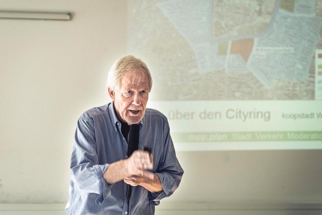 Ein Mann gestikuliert bei einem Vortrag.